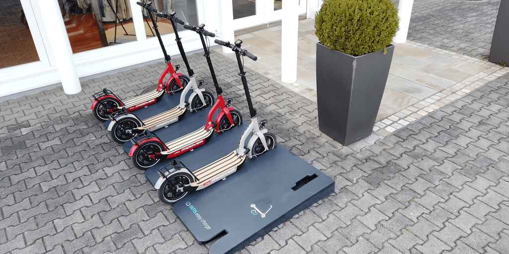 Four electric scooters charging on wireless inductive pad