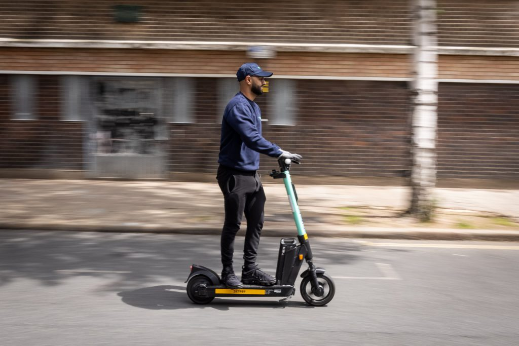 Man rides electric scooter on the road at speed