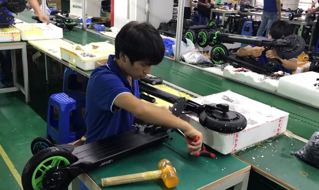 Man assembling an electric scooter for production