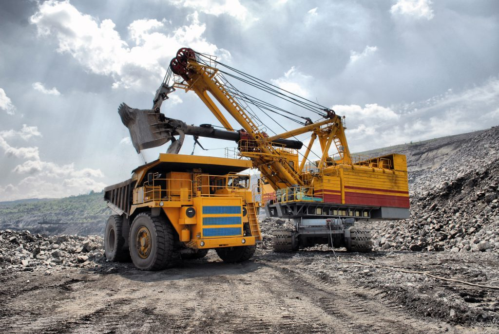 Two heavy mining vehicles collect resources